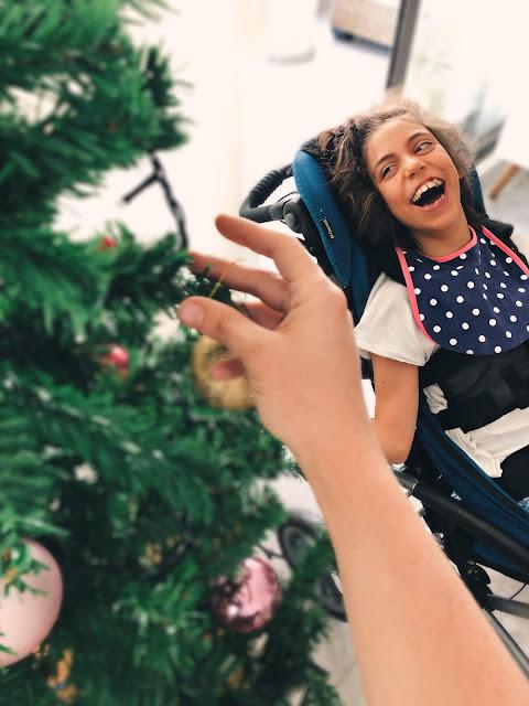 A la derecha, Rocío sonriente mirando el árbol de Navidad que está a la izquierda. Al medio una mano sostiene un adorno navideño.