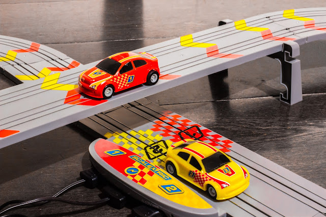 The crossing point of the track and a red car on the high road and yellow car on the low road
