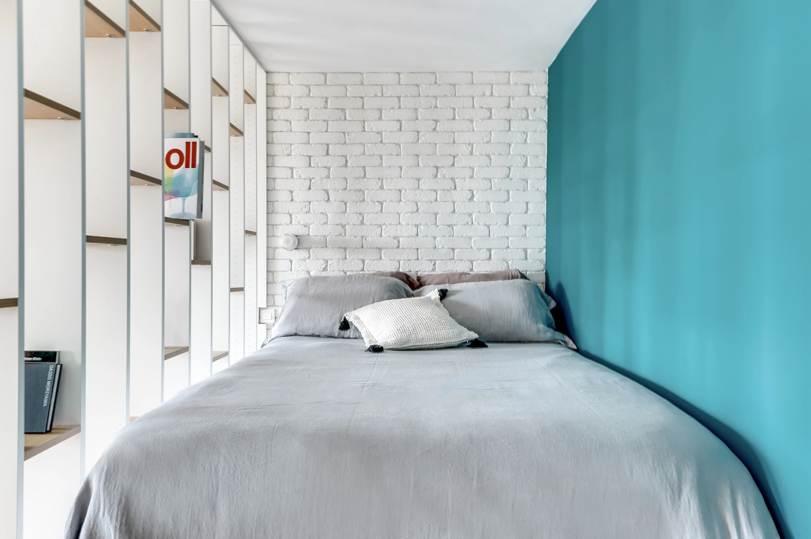 Bedroom in a small apartment, blue painted wall, naked bricks