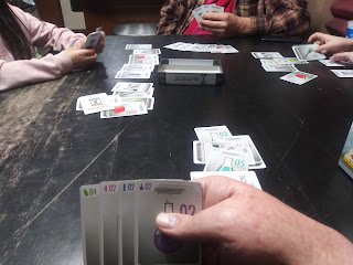 A game of Antidote in progress. Three players can be seen across the table from the point of view of the current player, who's holding his cards up where they can be seen. The current player's hand consists of a light green 4, a pink 2, a blue 2, and a purple 2. Several piles of cards can be seen in front of each player. The box lid is face down in the centre of the table, with an additional card in it.