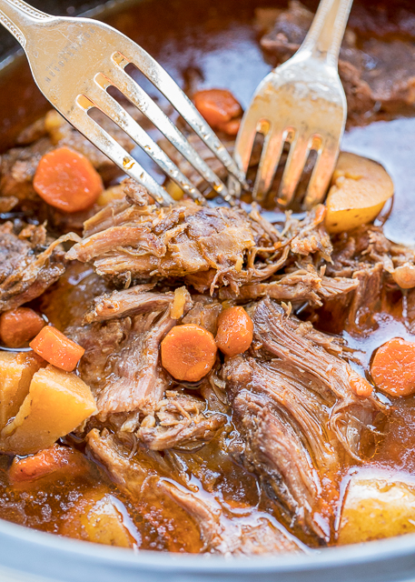 Slow Cooker Guinness Pot Roast - the BEST pot roast EVER! Pot roast, gravy mix, Italian dressing mix, tomato paste, carrots and potatoes. Put everything in the slow cooker and let it cook all day. Serve over mashed potatoes, grits or rice. PERFECT for St. Patrick's Day!! #slowcooker #stpatricksday #potroast