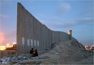 palestinian women next to the separation wall