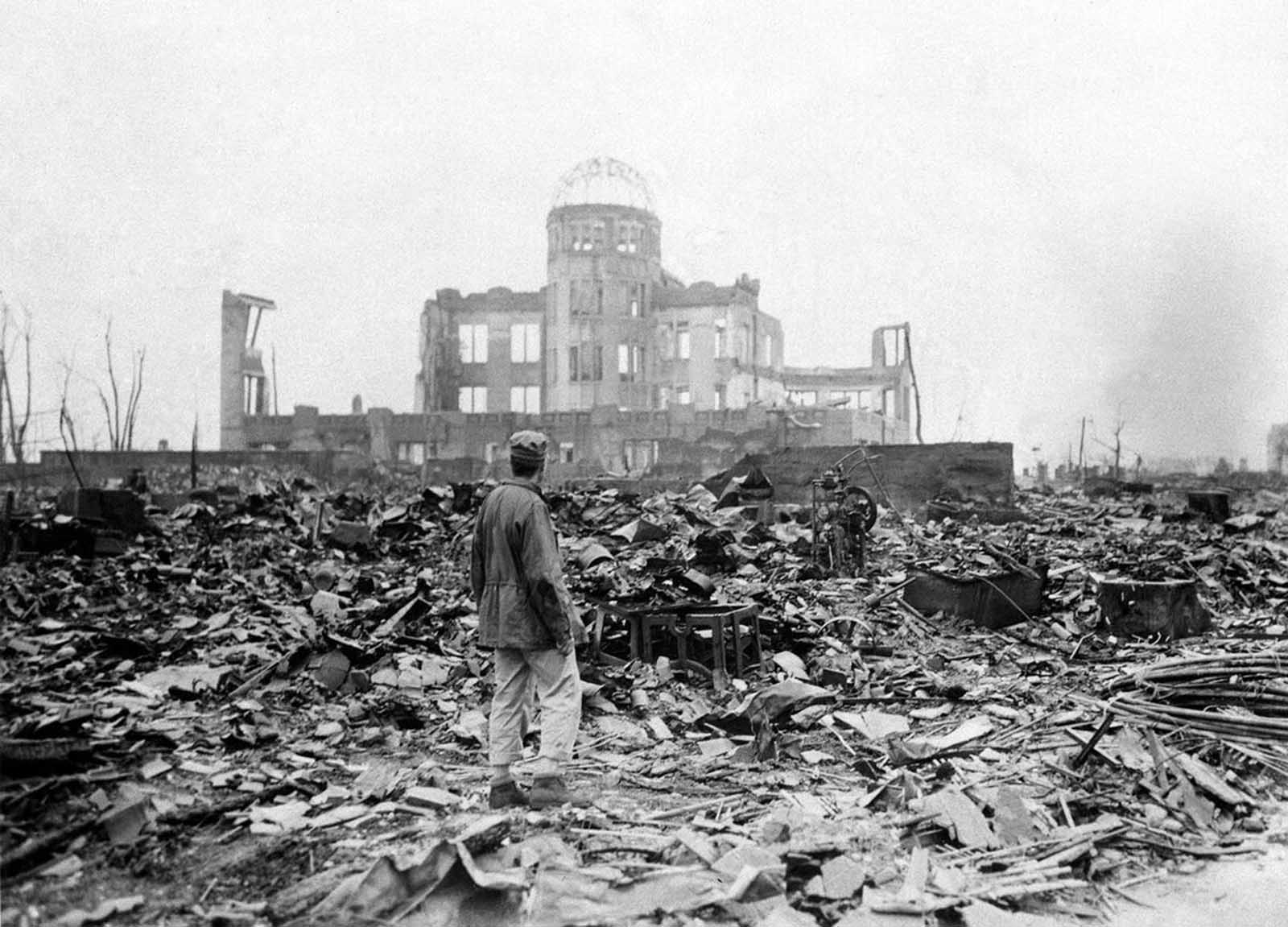 An allied correspondent stands in the radioactive rubble in front of the shell of a building that once was an exhibition hall in Hiroshima, Japan, one month after the first atomic bomb ever used in warfare was dropped on the city by the U.S. The explosion took place almost directly above the dome.