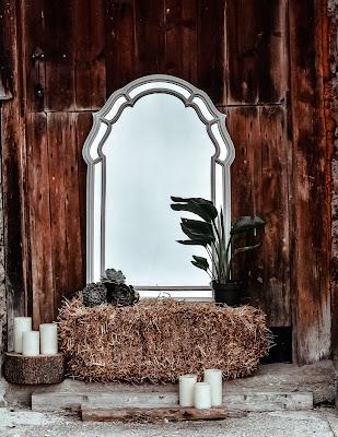 Decoracion exterior para una boda invernal con espejo, velas, balas de heno y piñas