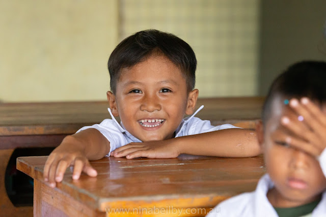 Young kindergarten boy smiles from ear to ear.