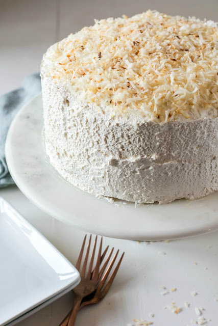 whole haleakala cake with toasted coconut and pineapple with forks and serving plates