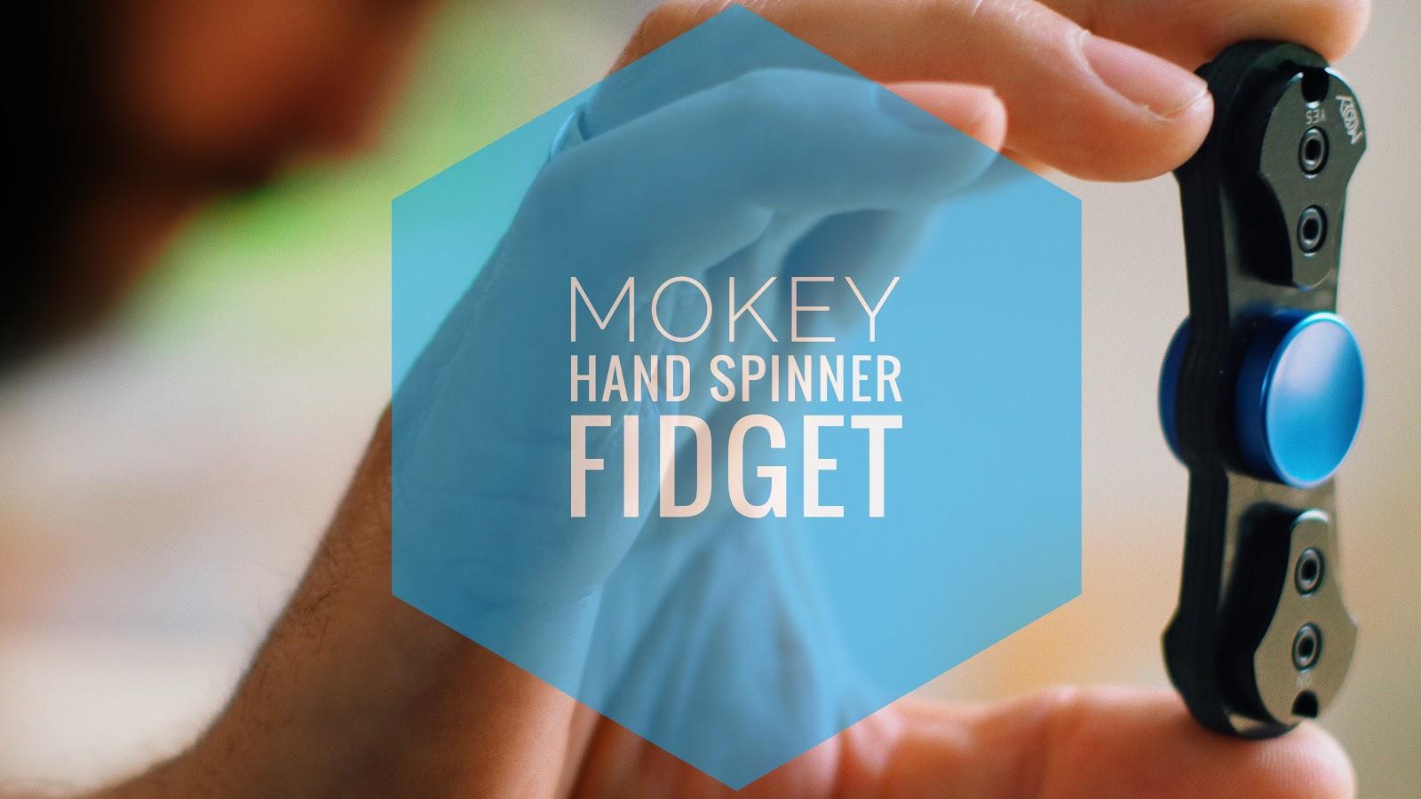 Fidget von Mokey in der Hand ein Logo in der Mitte und ein Kopf in der Unschärfe auf der linken Seite