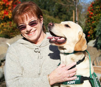 Jerri (wearing sunglasses) smiles with her arms around yellow Lab guide dog puppy Ursalyn in front of the pond on the San Rafael campus.