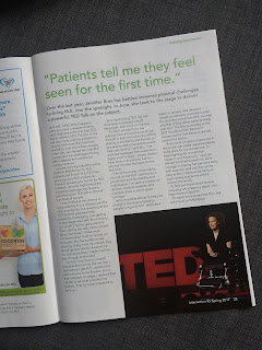 Photograph of an article in the InterAction magazine. Jennifer is sat in her electric wheelchair on stage at the TED Summit