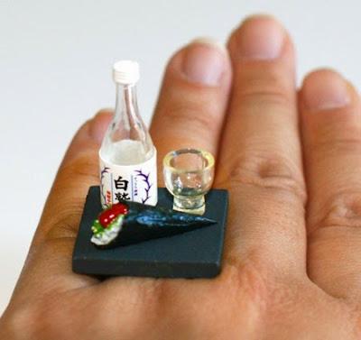 Uñas bien pintadas y mano con un anillo de botella con su vaso