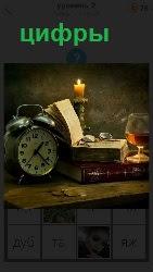 на столе будильник с цифрами, книга, свеча и бокал вина