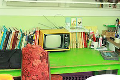 Beth Spencer's work space, with a green desk, books, and a small TV.