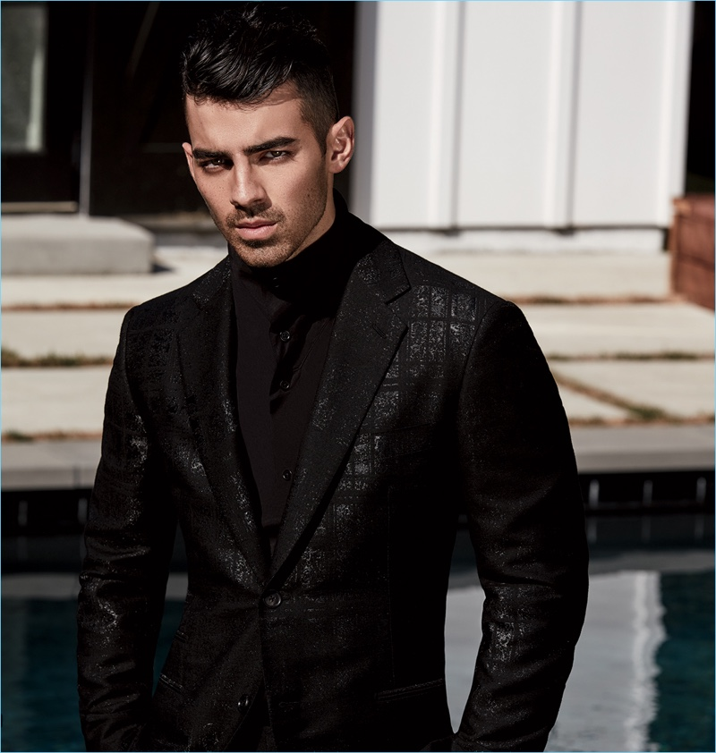 Joe Jonas wears a shirt, jacket, and trousers by Hermes
