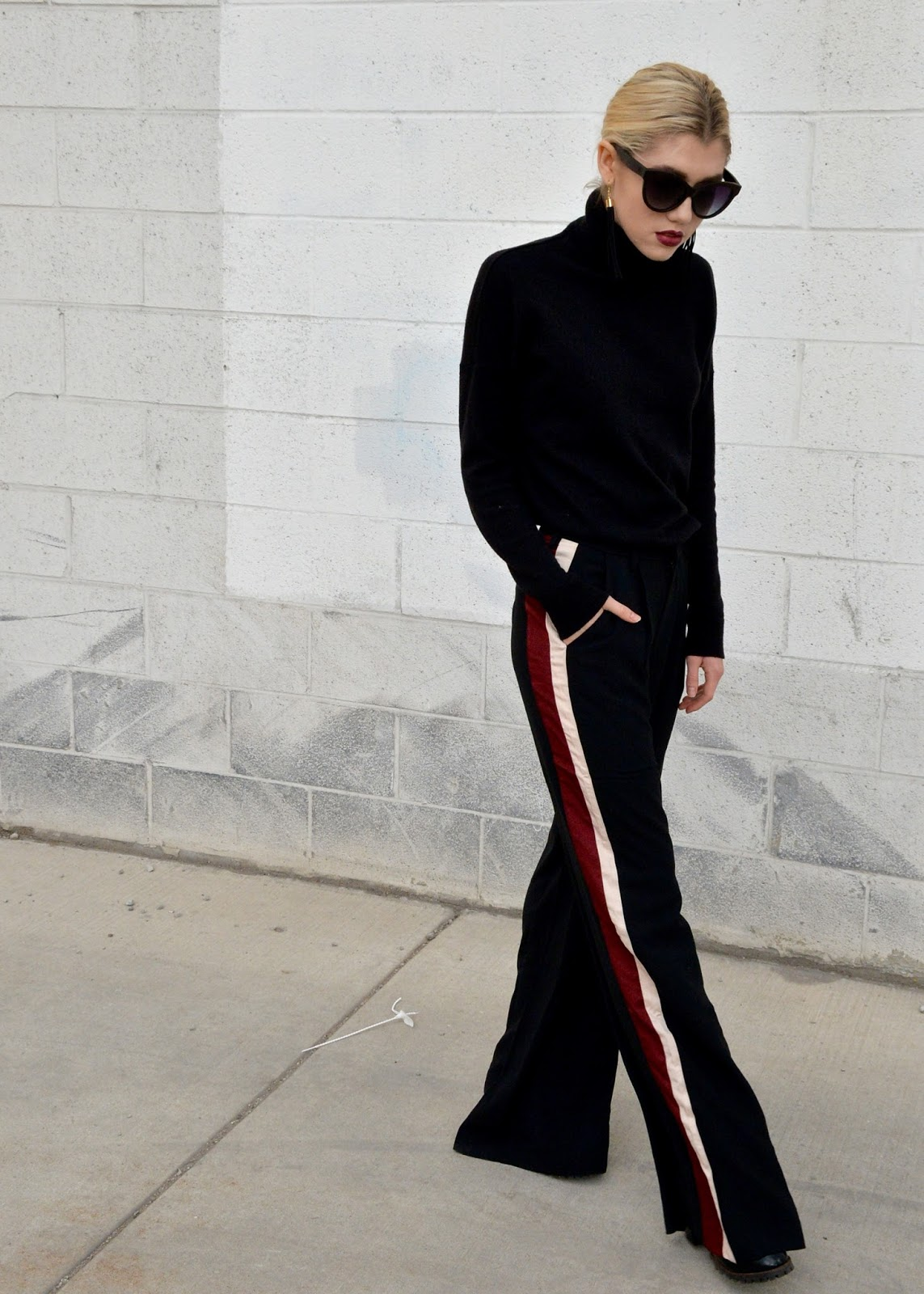 Walking in wide-leg pants with an all black outfit.