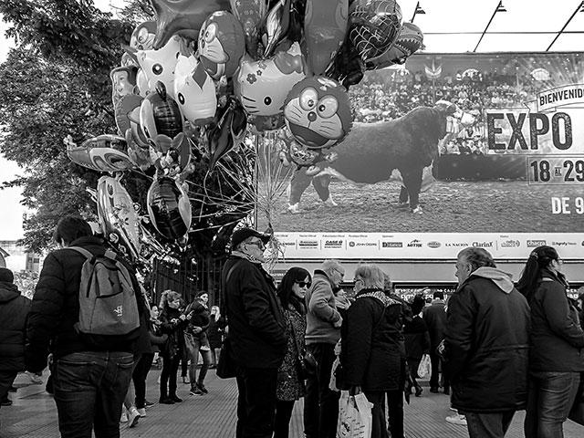 ByN.Persona vendiendo globos frente a la Exposición Rural.