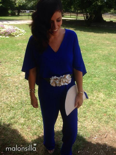 Invitada de boda con mono de Zara azul klein, cinturón de flores blanco y dorado y bolso abanico bicolor Malonsilla