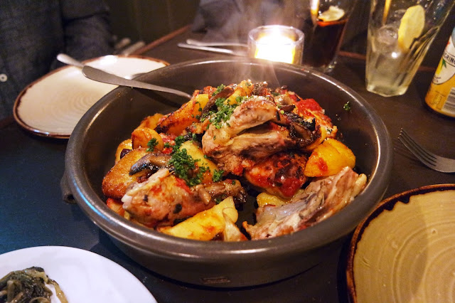 a large black dish with steaming pieces of chicken and potatoes in a tomato sauce