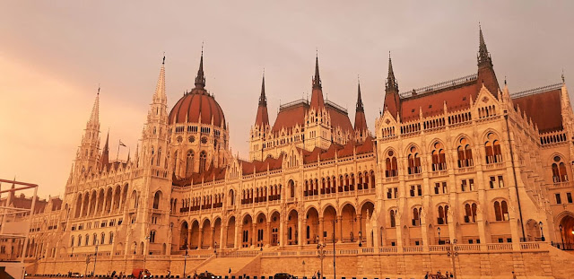 The stunning Budapest Parliament building - a large neo-gothic building with sand coloured brick and red rooftops