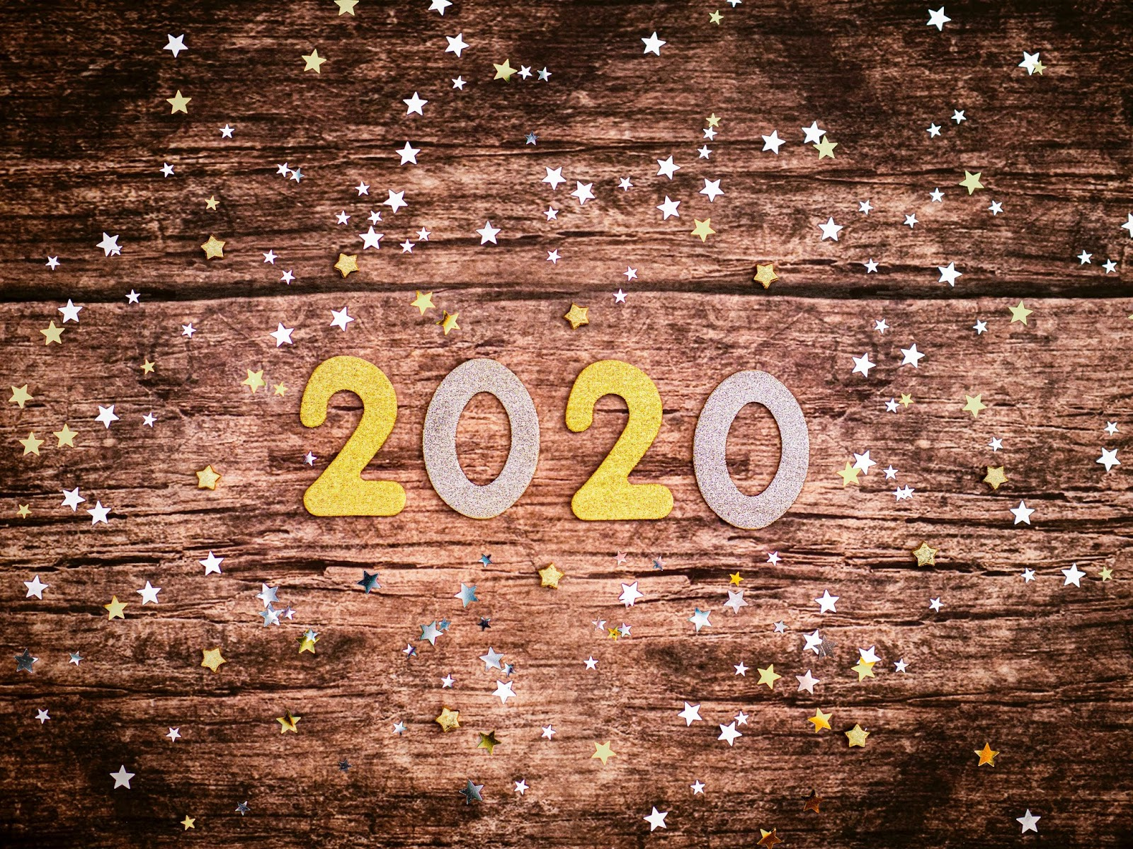 A photo of a foam and glitter 2020 in silver and gold on a dark brown wooden surface, with gold and silver foam and glitter stars surrounding them.