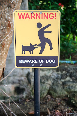 A humorous beware of dog sign shows a dog biting someone