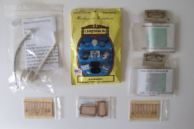 Selection of modern dolls' house miniature kits displayed on a tabletop.