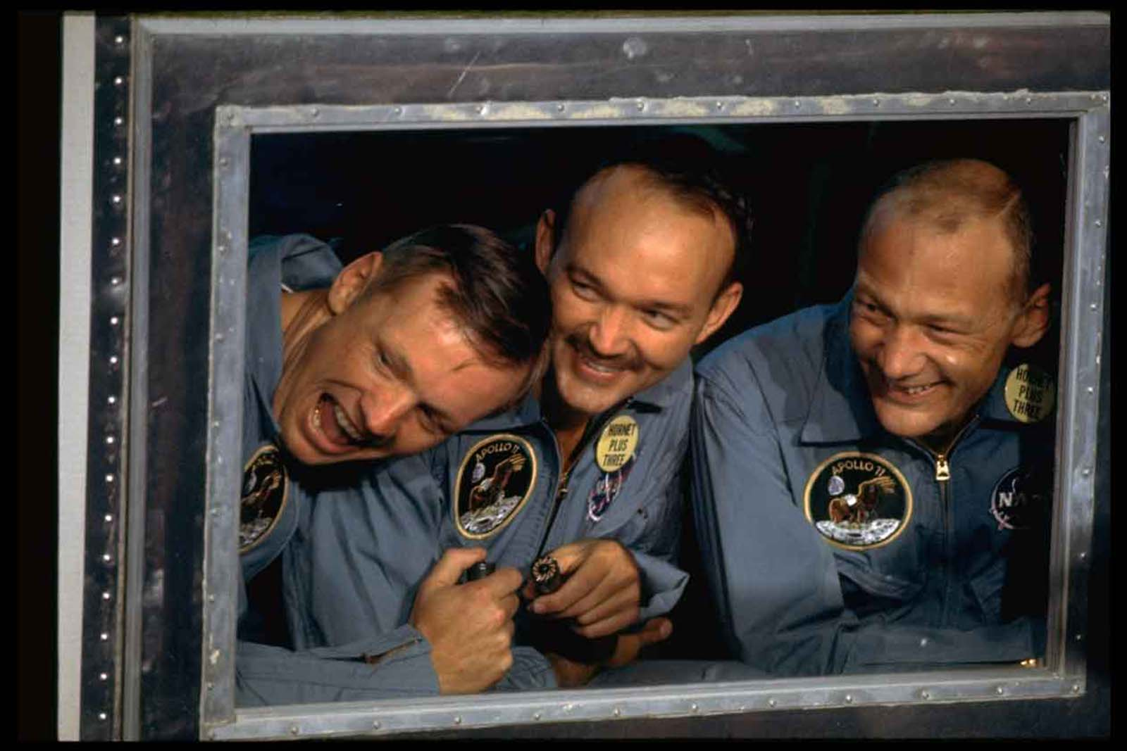 Apollo 11 astronauts (R-L) Aldrin, Collins, & Armstrong peering out window of quarantine room aboard recovery ship Hornet following splashdown fr. historic moon mission.
