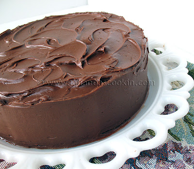 A close up photo of a Nigella\'s old fashioned chocolate cake resting on a white cake stand.