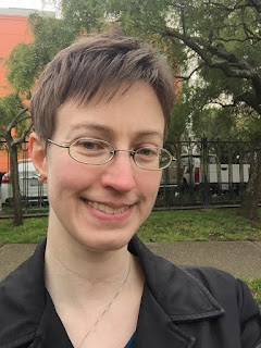image: photo of a white person with short light brown hair and glasses, smiling