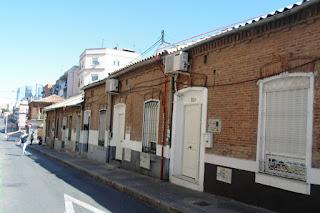Calle típica del barrio con antiguas casas bajas de ladrillo.