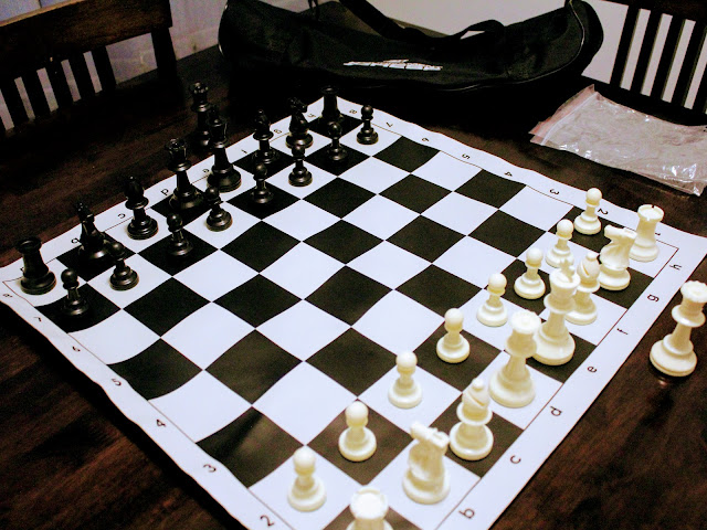 Tournament Roll-up Triple Weighted Chess Set - A chess set on a wooden kitchen table.
