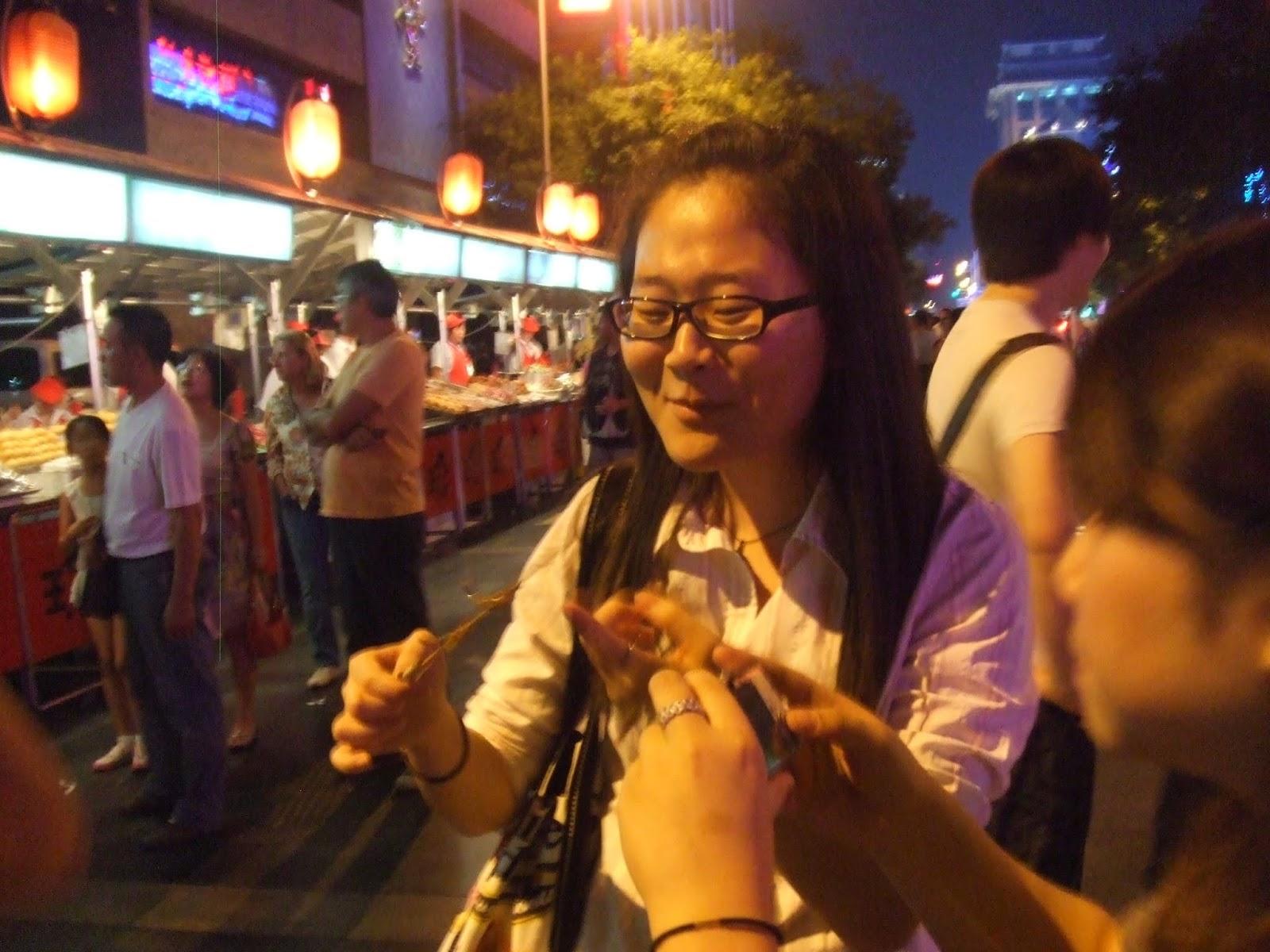 Chinesin mit Skorpionspieß bei Nacht