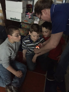Teacher showing three young boys a light