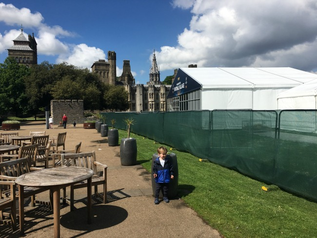 a-toddler-explores-cardiff-castle-world-war-two-shelters-view-of-inside-castle-with-toddler-posing-infront-of-football-fans-marquees