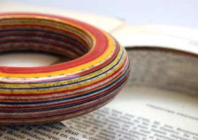 striped bracelet made of layers of paper in red, yellow, blue and book page text