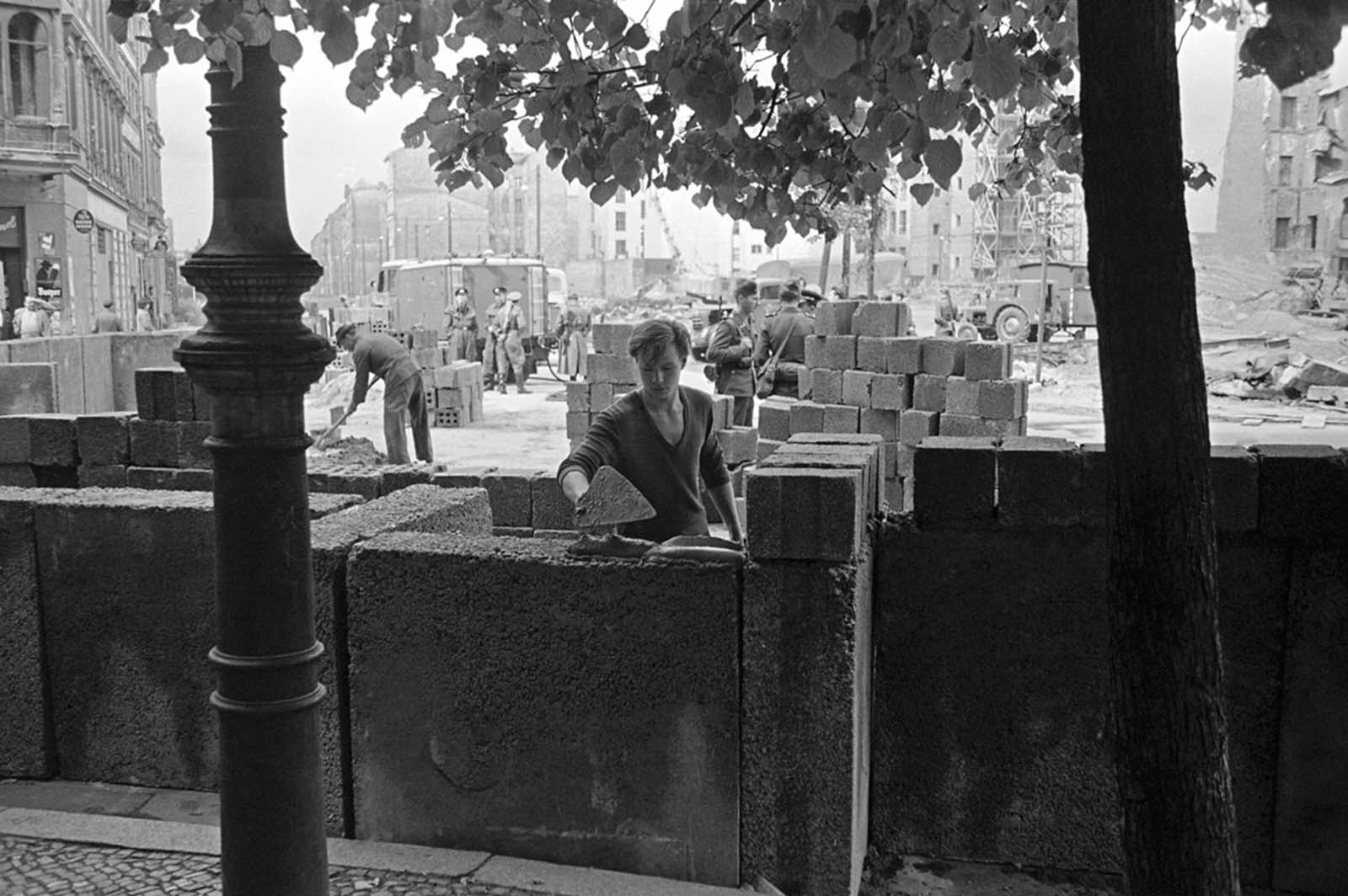A young East Berliner works on a concrete wall that was later topped by barbed wire at a sector border in the divided city on August 18, 1961. People's Police stand guard in the background as another worker mixes cement.