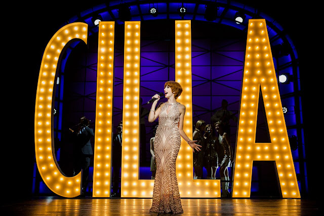kara lily hayworth wearing a floor length gold dress, singing in front of a giant illuminated CILLA sign