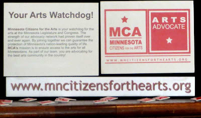 Display for Minnesota Citizens for the Arts with web address sign reading mncitizensforthearts.org