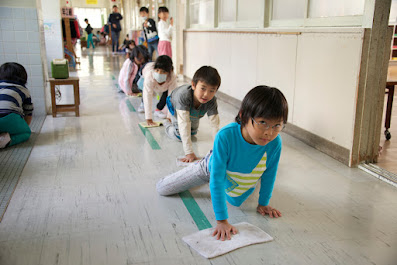crianças japonesas fazendo faxina limpando chão na escola