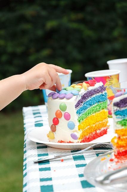 Kind greift nach Regenbogenkuchen