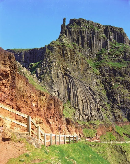 Irish Harp and Chimney Tops. Looking S. The footpath cut in the Interbasaltic Bed underlies the irregular columns of the first flow of the tholeiitic basalts. The isolated columns of the Chimney Tops are part of the second flow and a small part of the third flow is seen at the cliff top.