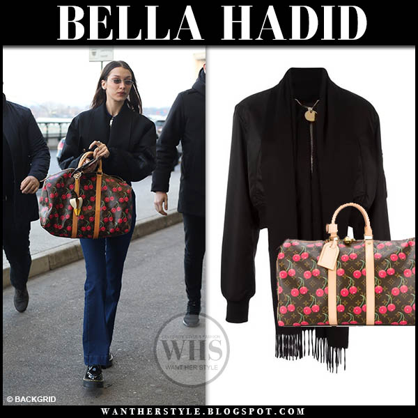 Bella Hadid in black bomber givenchy jacket, jeans with louis vuitton cherry print duffel bag off duty airport style january 13