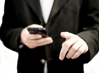 a man in a suit with an iphone
