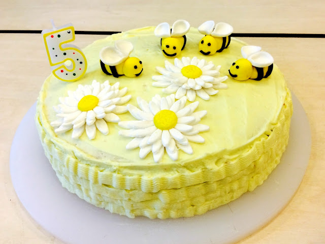 Butter cake with buttercream frosting and fondant bumblebees and flowers