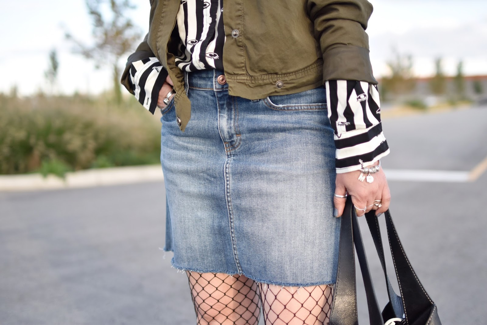Monika Faulkner outfit inspiration - denim mini skirt, fishnet tights, black-and-white patterned shirt, olive cargo jacket