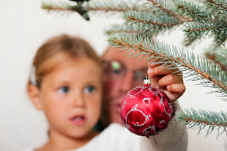Photo of a child and his father hanging an ornament on a Christmas tree branch