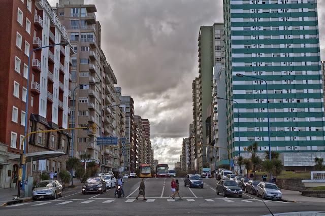 Peatones cruzando con fondo nuboso.