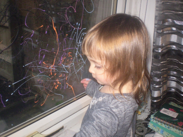 Eldest creating artwork on a window