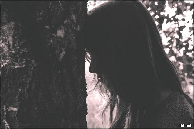 ảnh cô gái buồn dựa đầu vào cây