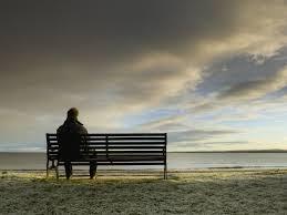 un hombre aparece sentado sólo frente al mar