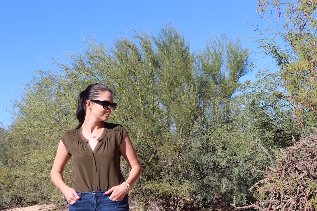 In this photo wearing a silk blouse, cat eye sunglasses and jeans, I am standing in the middle of the desert looking down.